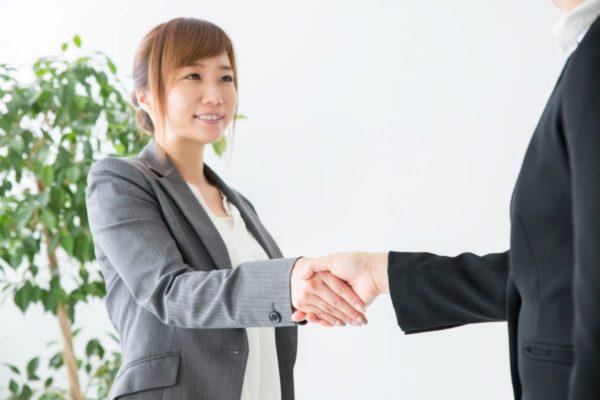 握手するスーツの女性