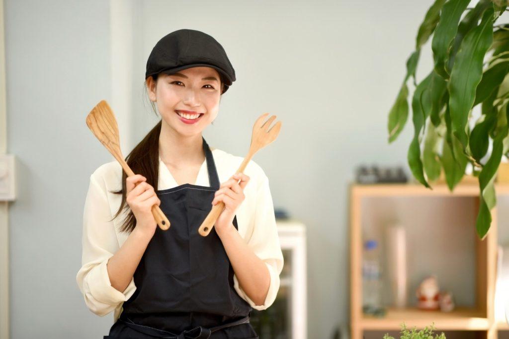 キッチン用品を持つ女性