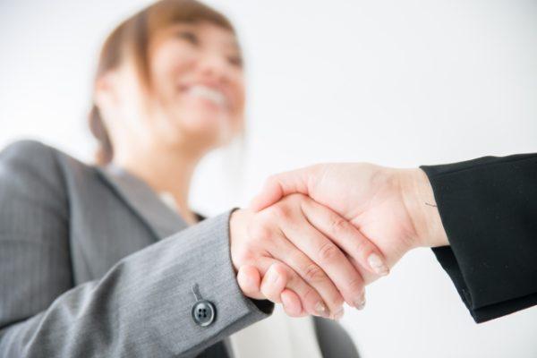 取引先と握手を交わす女性