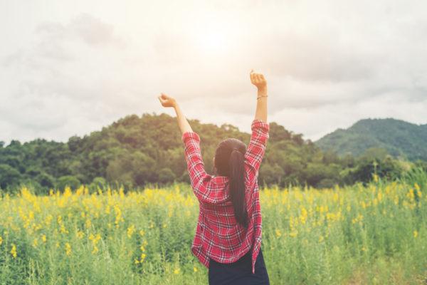 草原で万歳する女性