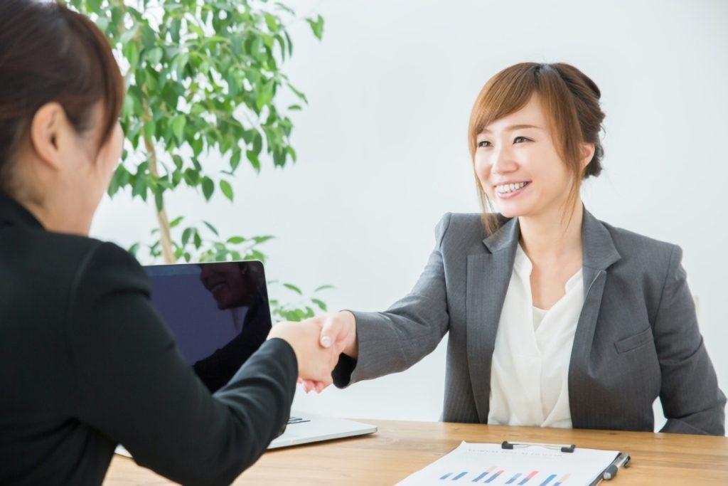 契約成立で握手をするビジネスウーマン