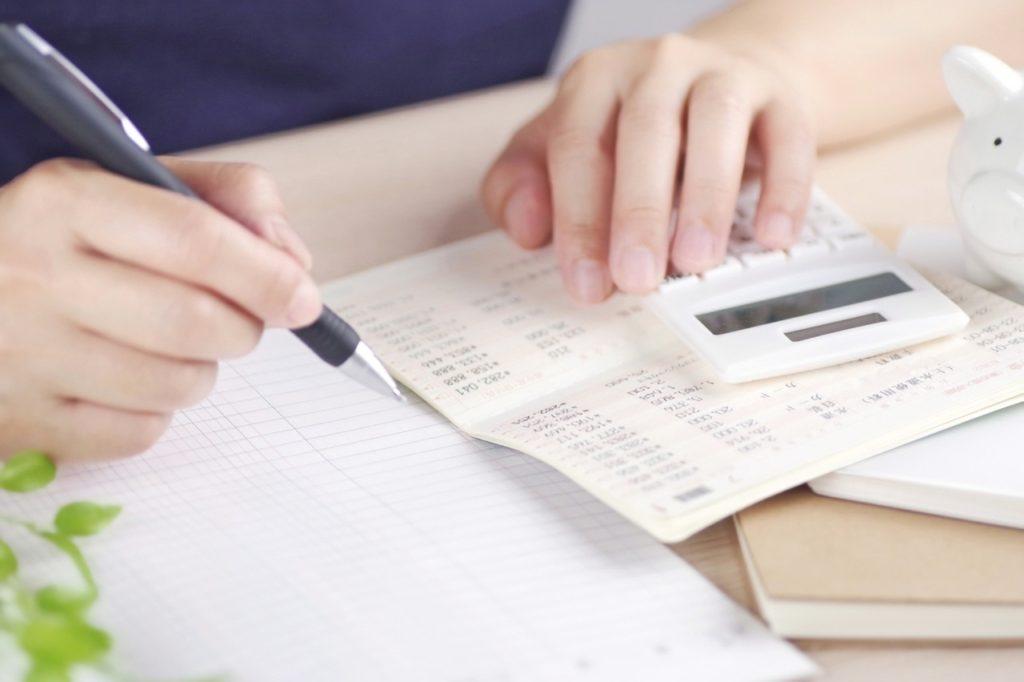お金を計算する女性の写真