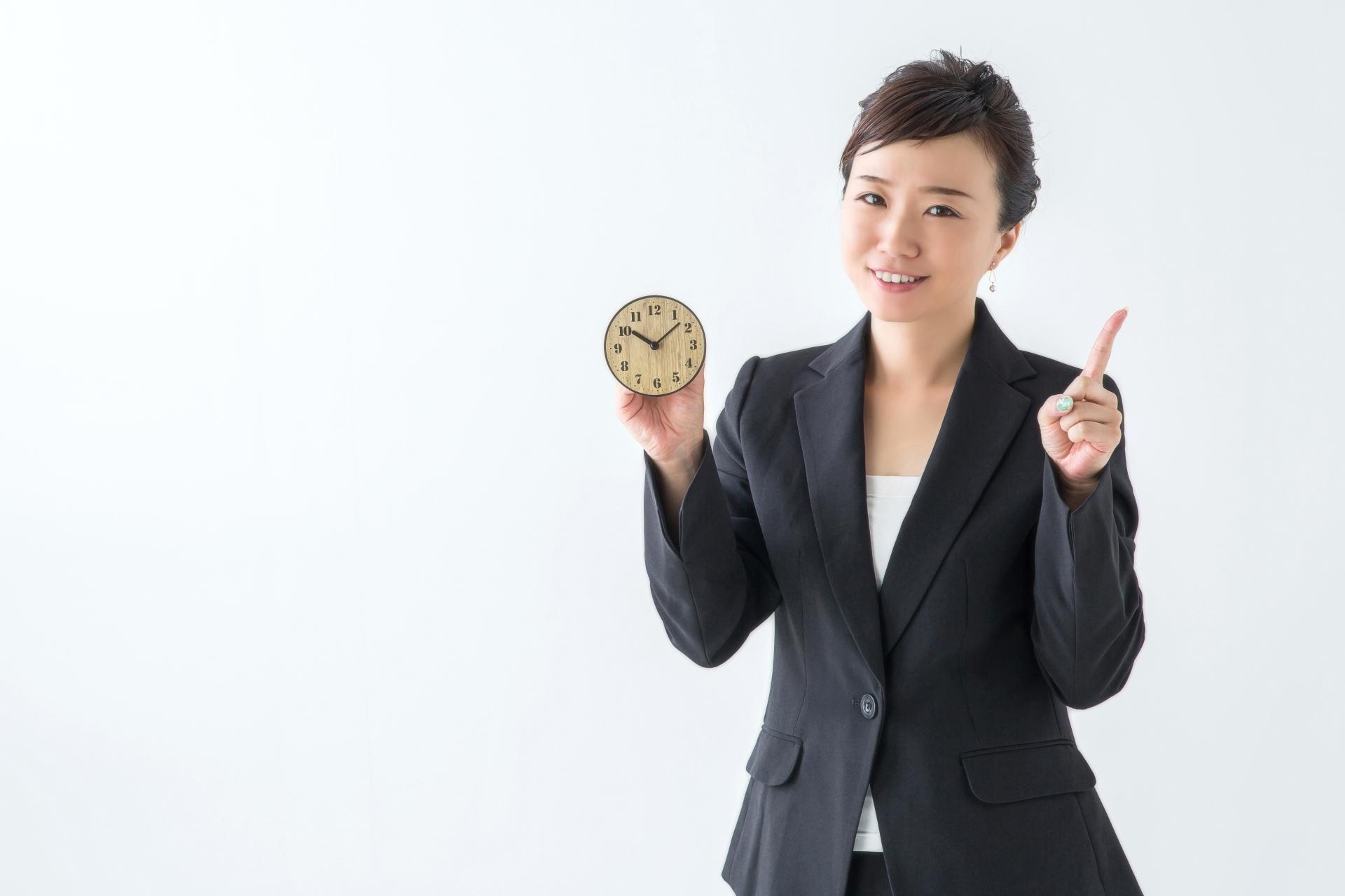 時計を持つスーツ姿の女性