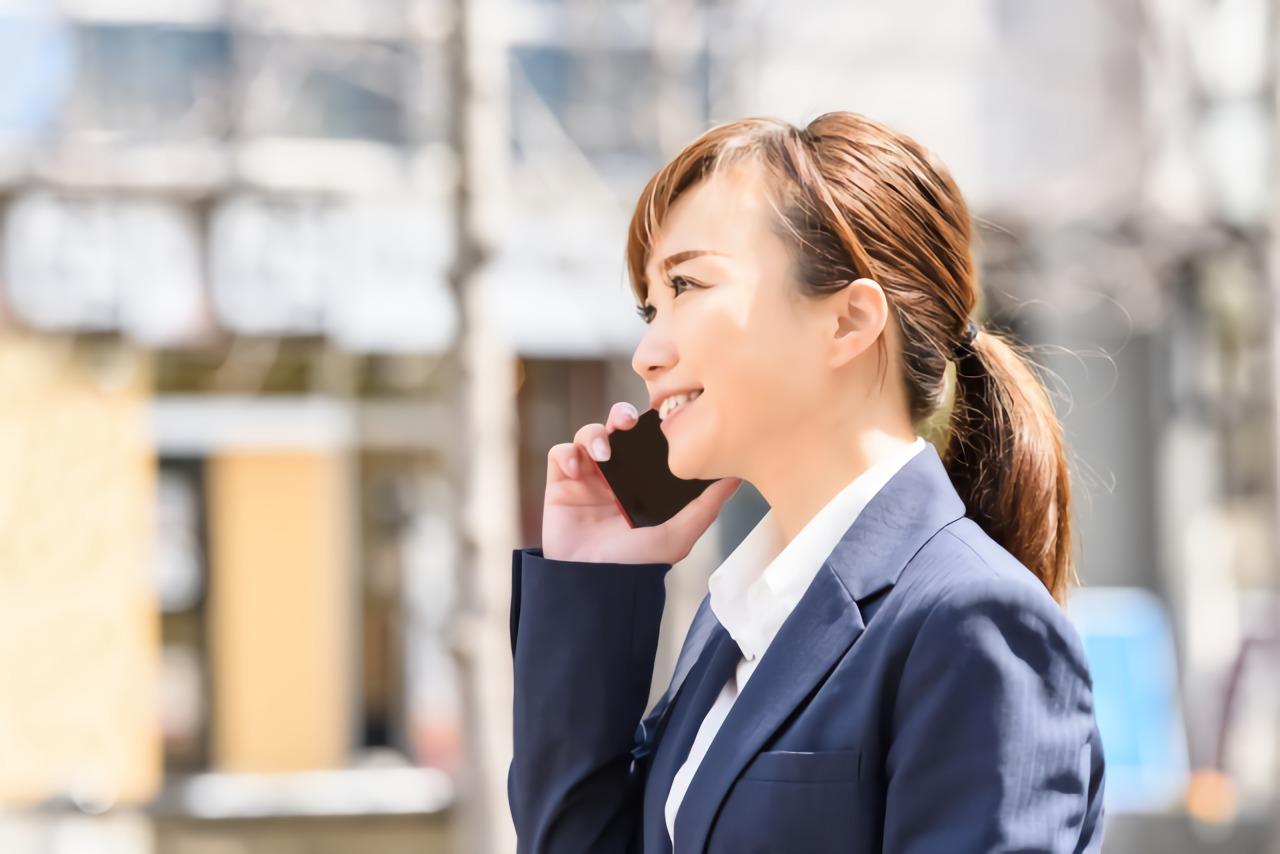 携帯で電話をかけるスーツの女性