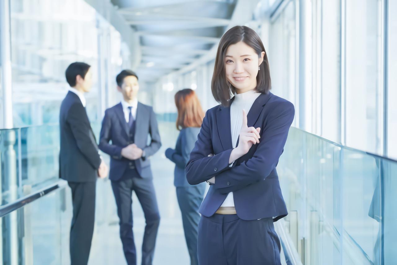 笑顔でポイントを示すスーツの女性
