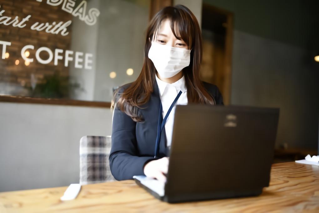 パソコンをするマスク姿の女性